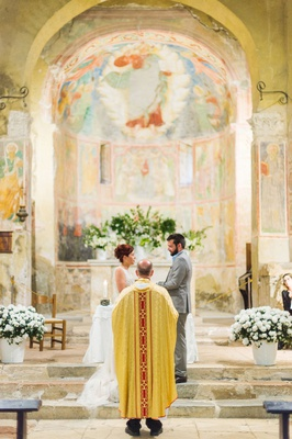 bride and groom at stone altar italy destination wedding fresco paintings on walls abbey venue