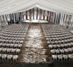 White and gray wedding ceremony with white drapes, grey carpet, and branches.