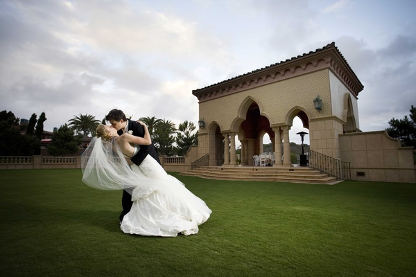 Bride and groom kiss at Grand Del Mar outside