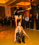 Female acrobat in black, gold outfit performs on the shoulders of a male acrobat at engagement party