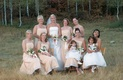 Bride with bridesmaids on chairs in countryside