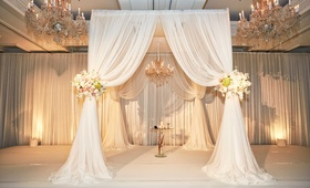Jewish wedding ceremony in Chicago with white drapes, flower tie backs with roses, chandeliers