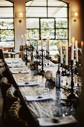 wedding reception table long with cobwebs spider black candelabra skulls wicker chairs