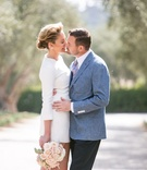 Bride in white mini dress and groom in casual blue jacket kiss