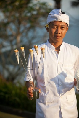 Balinese server holds sculpture of appetizer cones