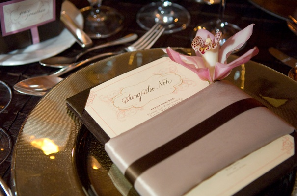 white menu card wrapped with taupe and brown striped ribbon