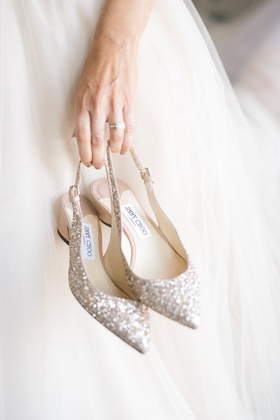 bride in wedding dress engagement ring holding jimmy choo glitter slingback pumps pointed toe