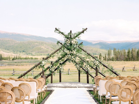 unique wedding ceremony made with six intersecting poles in a triangle