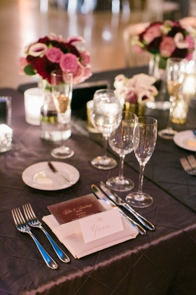 Dark wedding colors purple linens with menu in napkin and low centerpieces pink and purple blooms