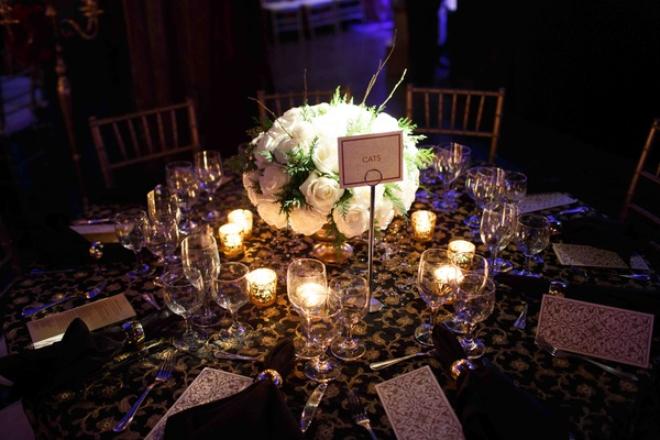 Wedding reception table with a centerpiece of white roses with greenery surrounded by votive candles