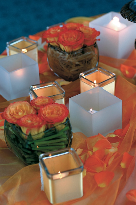 Orange flowers in vases and votive candles