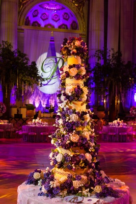 Tall six layer cake with purple and cream flowers