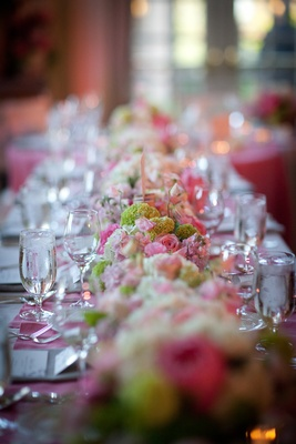 Wedding reception table with a floral runner of green and white hydrangeas and pink and white roses
