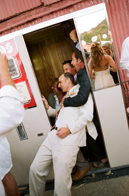 Groom with friends in outdoor wedding photobooth