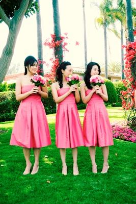 bridesmaids wearing pink gowns carry pink bouquets