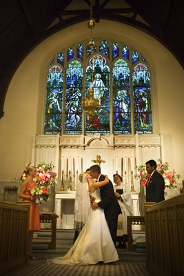 Bride and groom kiss at church altar in wedding