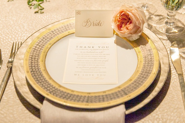 white and gold calligraphy thanks you note on yellow charger plates at the reception