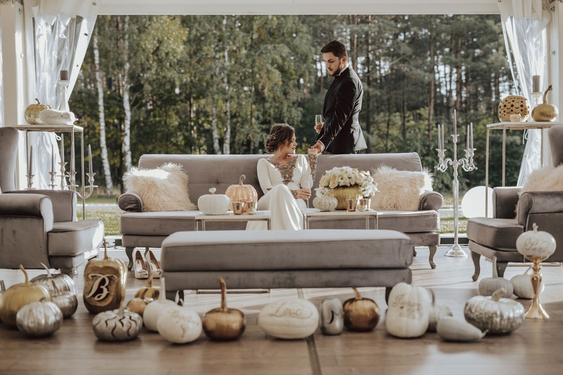 bride in wedding dress gold silver pumpkins velvet sofa armchair bench white flowers candelabra