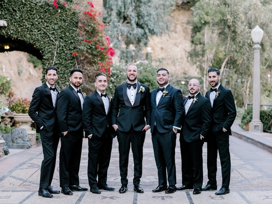 groom and groomsmen in classic black tuxedos and bow ties