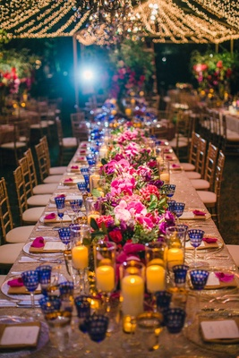 Head table at wedding with candlelight, pink flowers, blue goblets, and twinkle lights overhead