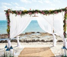 White fabric flower arch on beach for wedding ceremony