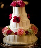 White cake with stripes, dots, and fresh pink flowers
