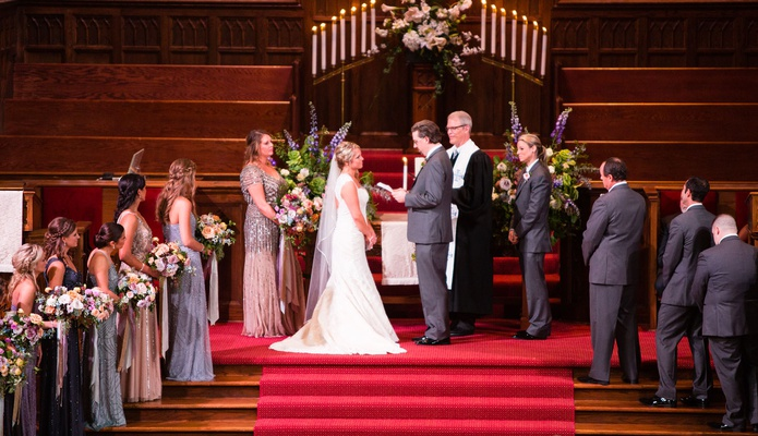 Wedding ceremony bride and groom at front of church red carpet wood stairs beaded bridesmaid gowns