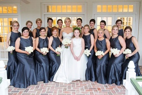 Bride in strapless wedding dress flower girl and bridesmaids in grey long silk gowns