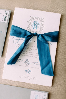 wedding invitation letterpress torn edge paper blue ribbon blue silver grey monogram script