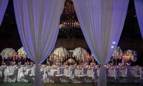 Wedding inspiration long table white flower centerpiece drapery drapes purple violet lighting