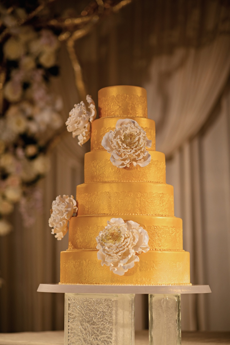 Six layer cake with gilt frosting and sugar flowers