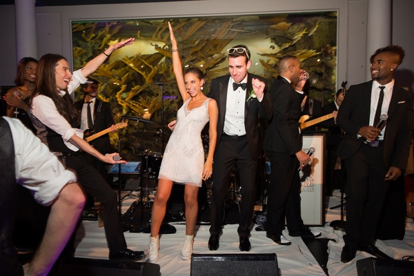 Bride in a short Monique Lhuillier gown and groom in black tuxedo dance with the band