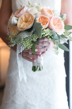 Bride holding orange garden rose and white rose bouquet