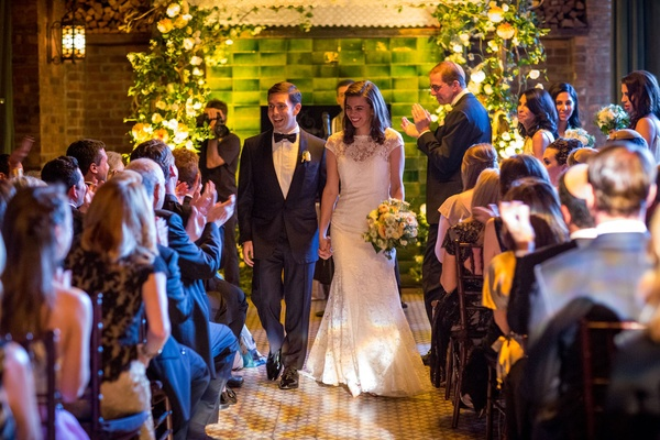 Wedding ceremony bride and groom walk up aisle hand holding green backdrop yellow flowers white