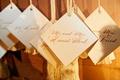 wedding reception escort card display on wall calligraphy white tassel diamond shape