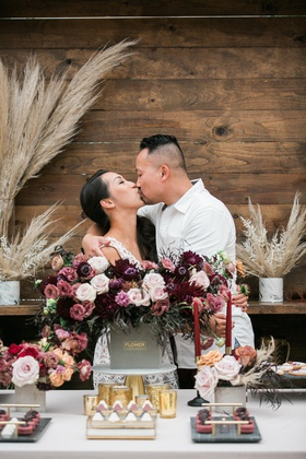 bride and groom kissing at bridal shower after groom delivers flowers