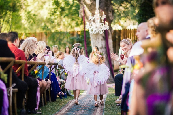 Barefoot flower girls with wings and pink dresses at outdoor bohemian wedding ceremony