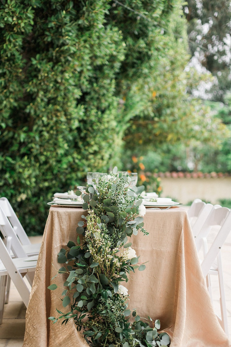Wedding reception at Eden Gardens, CA with foliage runner on table with golden taffeta tablecloth