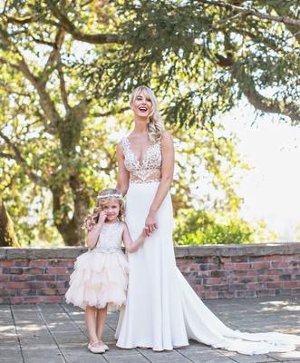 Bride in sheer cutout wedding dress with flower girl in cute dress layer ruffle skirt halo headband