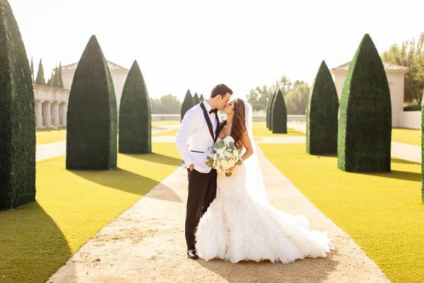 bride in ines di santo mermaid wedding dress with ruffles, groom in white tuxedo jacket