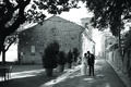 black and white photo of a bride and groom walking through tuscany