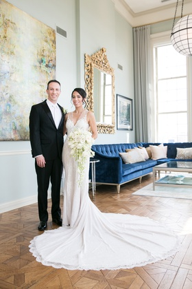 bride in rivini wedding dress with long train, groom in tux and white neck tie