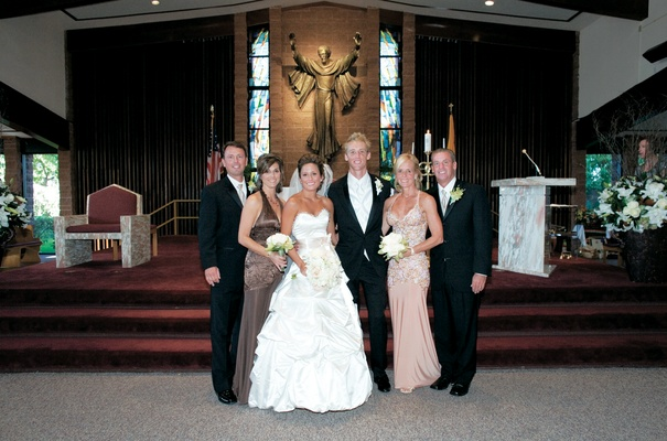 Wedding couple with parents in front of church
