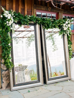 two large, framed mirrors as seating chart with heavy greenery