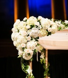 Corner of chuppah decorated with white rose, hydrangea, and orchid flowers with ivy