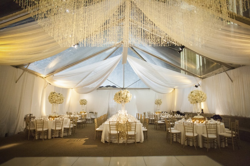 Tented Wedding Reception With White Draping Floral Arrangements Linens Gold Chairs