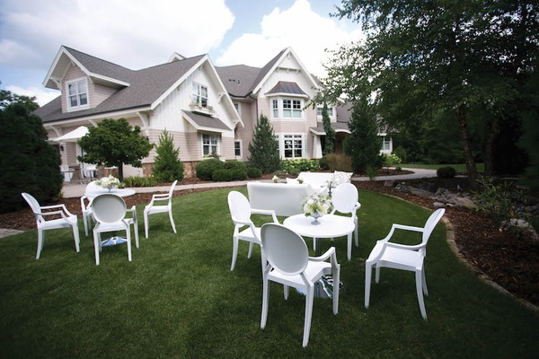 White round back chairs and tables on front lawn
