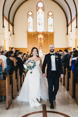 wedding recessional in catholic church, bride in lace wedding dress with overskirt, groom in tux