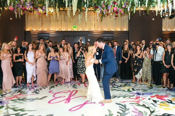 bride in strapless dress and groom in blue suit dancing on colorful dance floor as guests watch