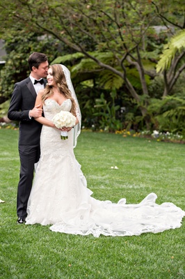 bride in kittychen couture lace gown and mantilla veil, groom in hugo boss forehead kiss